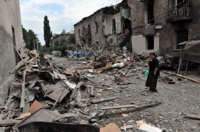 A Georgian woman yesterday passed by a building hit by bombardments in Gori. A Georgian government spokesman said that 60 civilians had been killed in airstrikes on the city. (Dimitar Dilkoff/ AFP/ Getty Images)